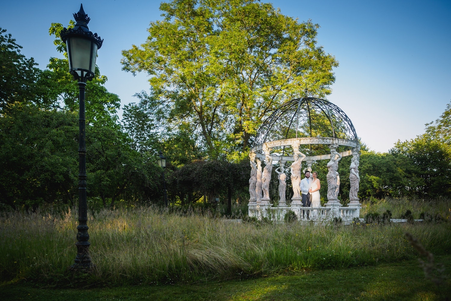 Bride and groom posing for wedding photographer in the grounds of Berwick Lodge Bristol