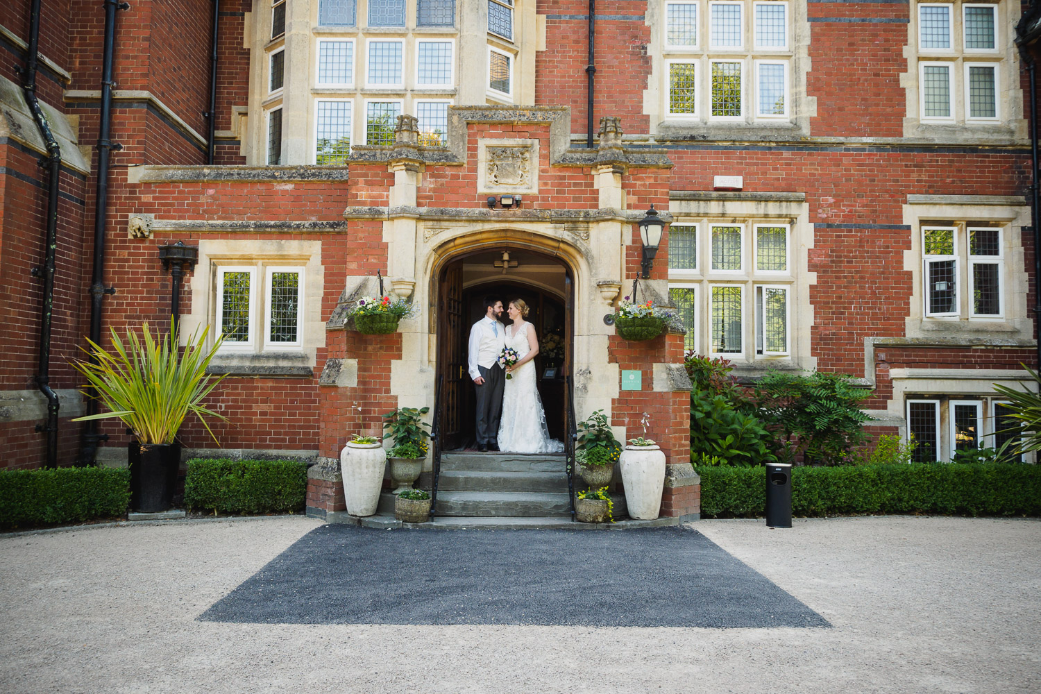 Bride and Groom standing in the entranceway of the wedding venue that is Berwick Lodge