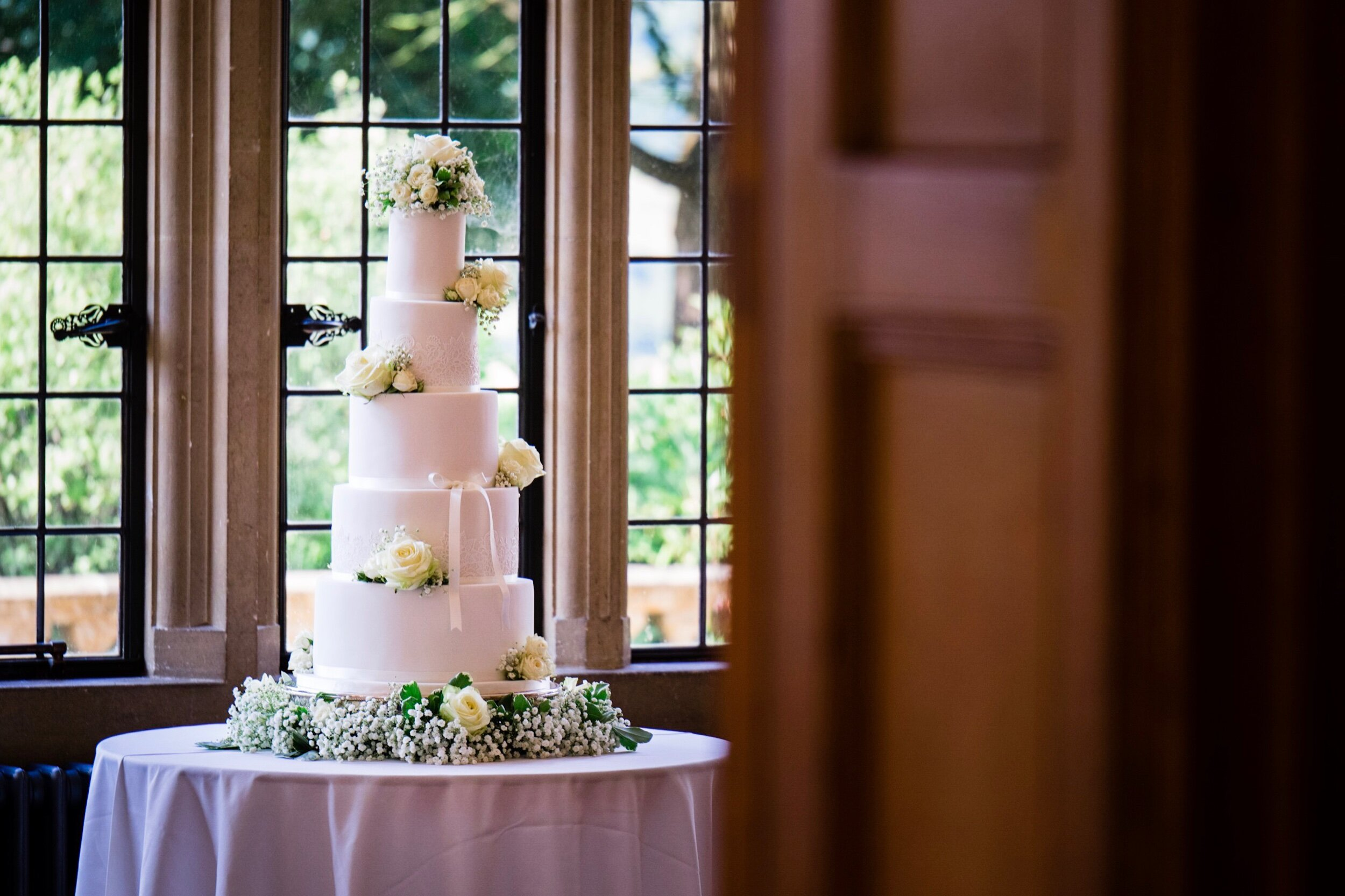 Gorgeous wedding cake next to a big window at a lovely wedding venue in Bristol