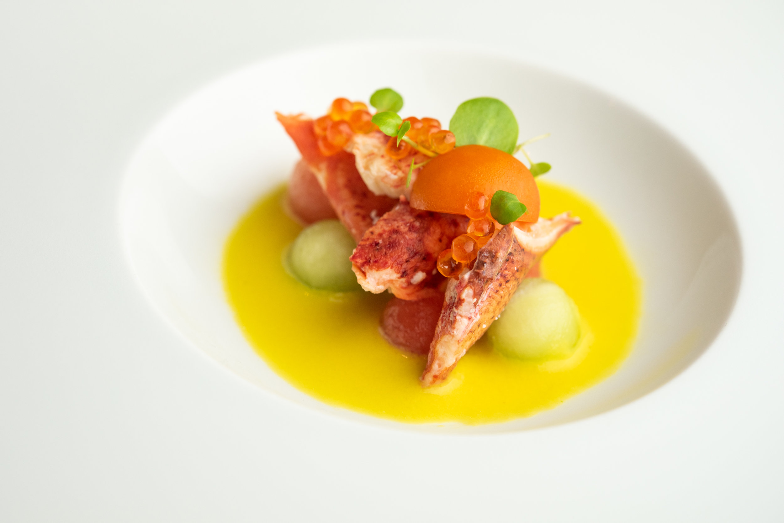 Yellow Tomato Gazpacho with maine lobster, compressed melon, and trout roe.
