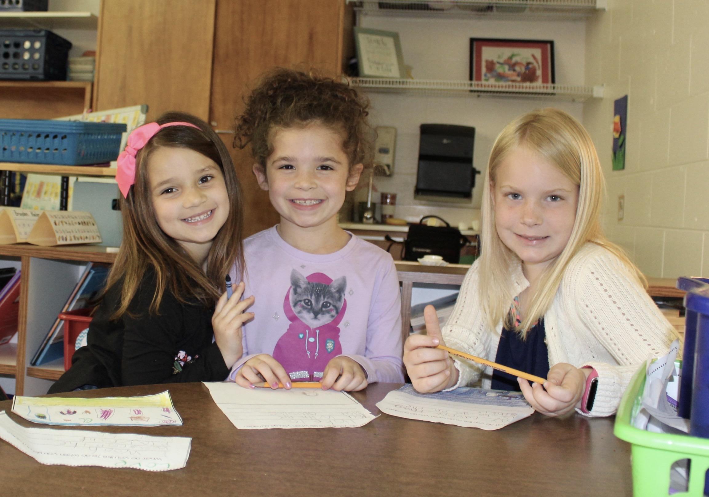 Three smiley girls working at desk