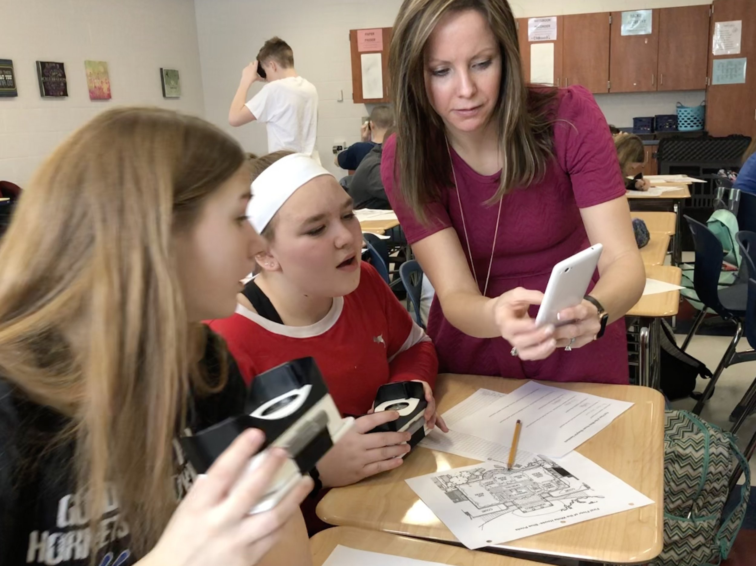 Teacher working with students using VR viewfinders as part of a project.