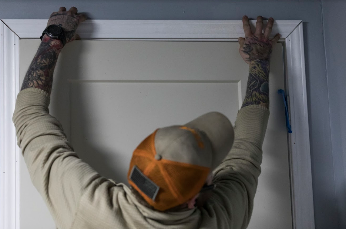Patterson lines up the newly cut trim above a door in his house.