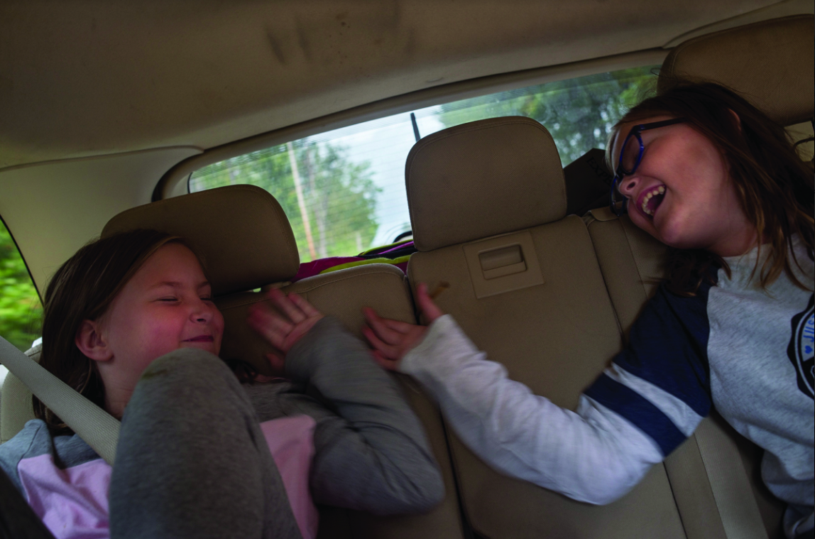 Ella and Rylie play fight in the back of Apryl's car while on their way back from cherry picking.