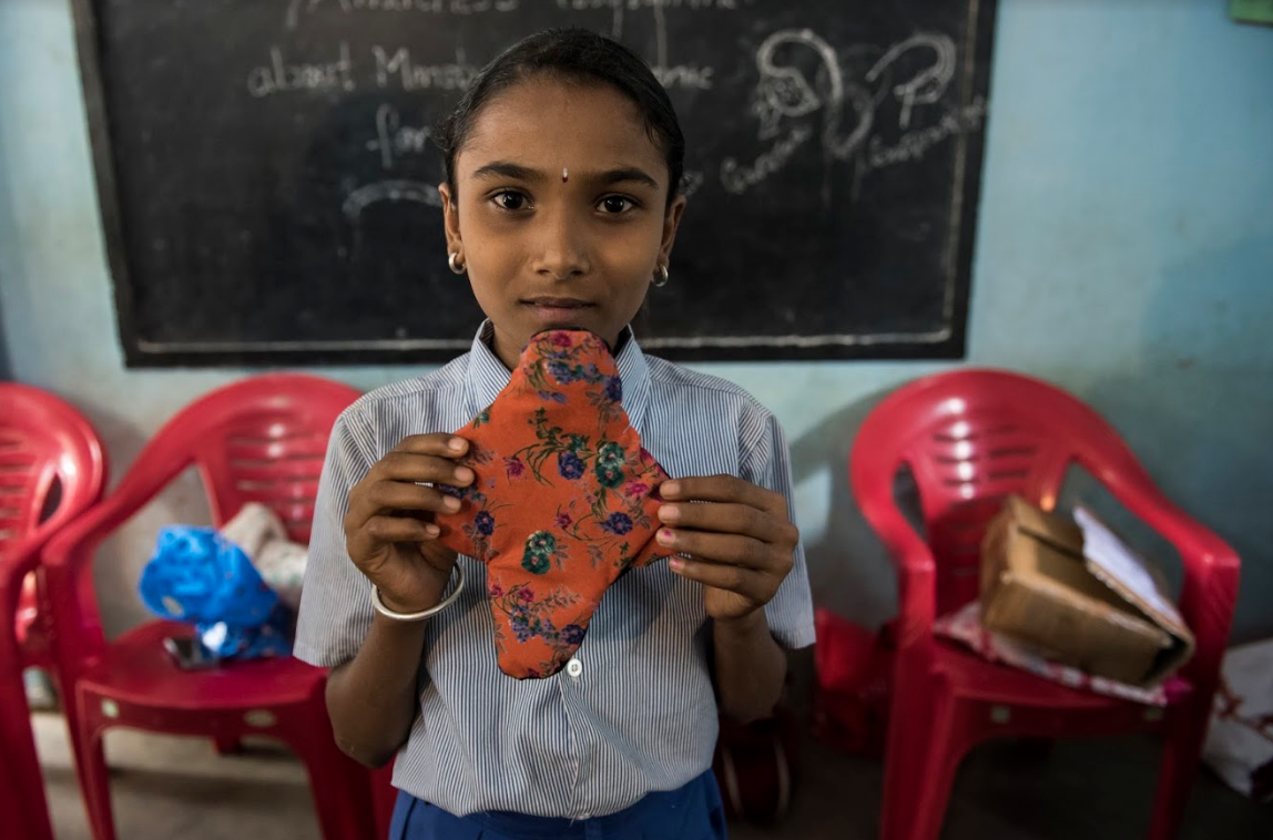 A girl holds up a reusable cloth sanitary pad she made during the first ever Ruby Days curriculum workshop.
