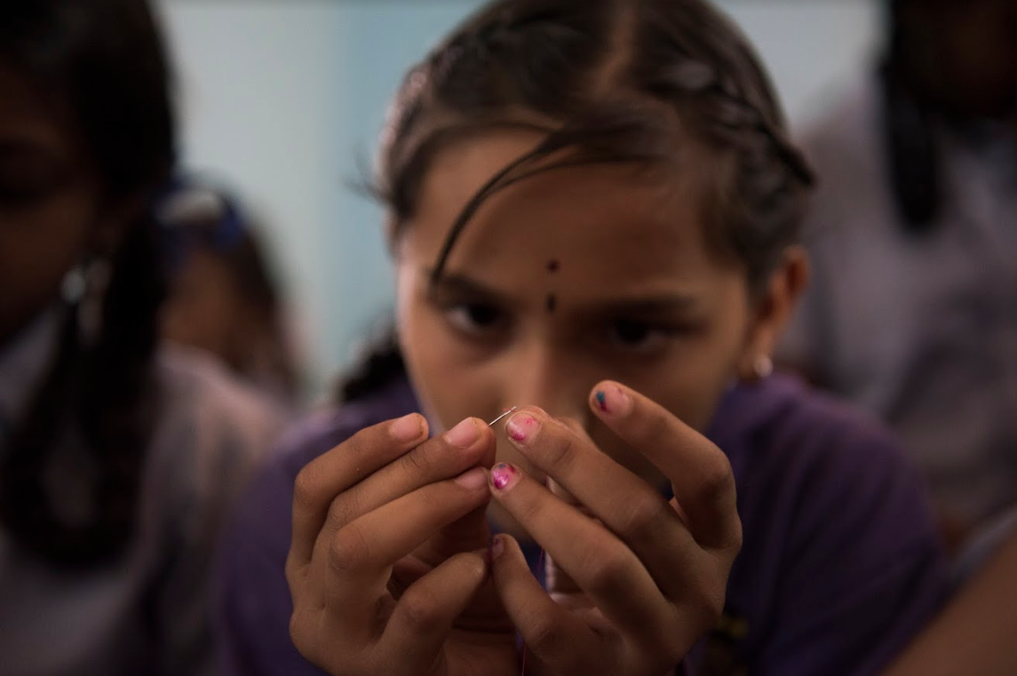 A student threads her needle as she prepares to stitch a cloth sanitary pad.