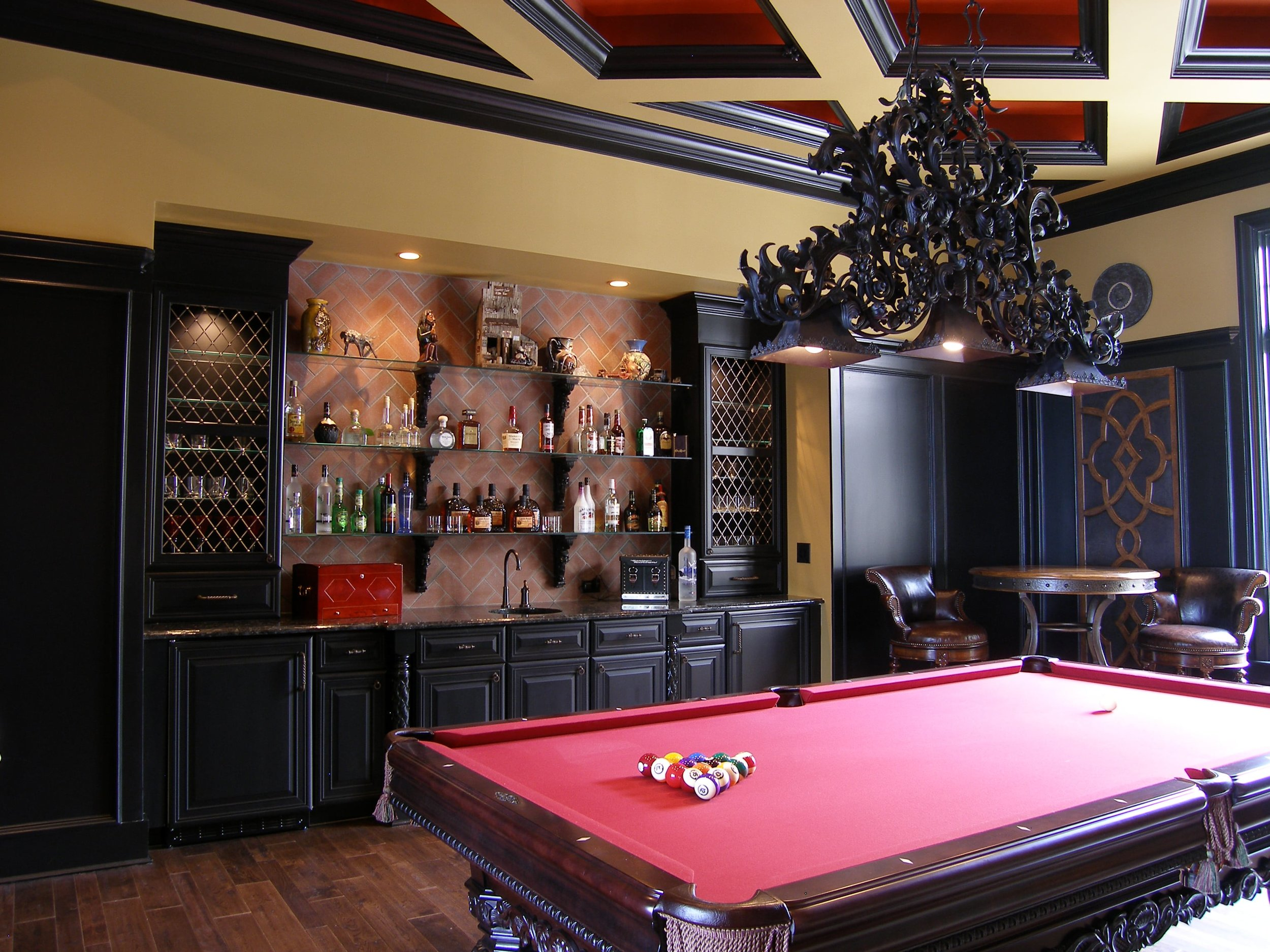 Billiards Room with custom coffered ceiling and built in bar. Brick back splash adds to the old world feel of the home.