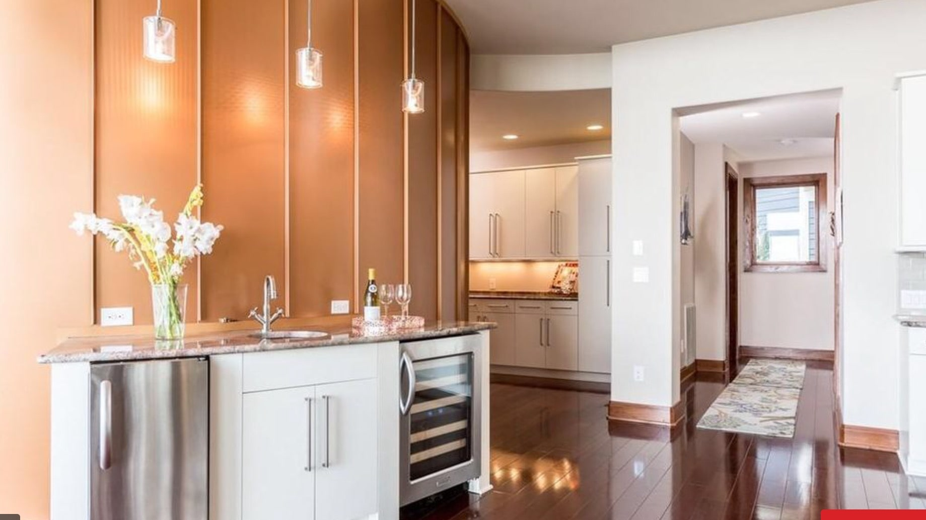 Curved wet bar perfect for entertaining.  The pendant lights pop against the copper colored standing seam metal curved wall.