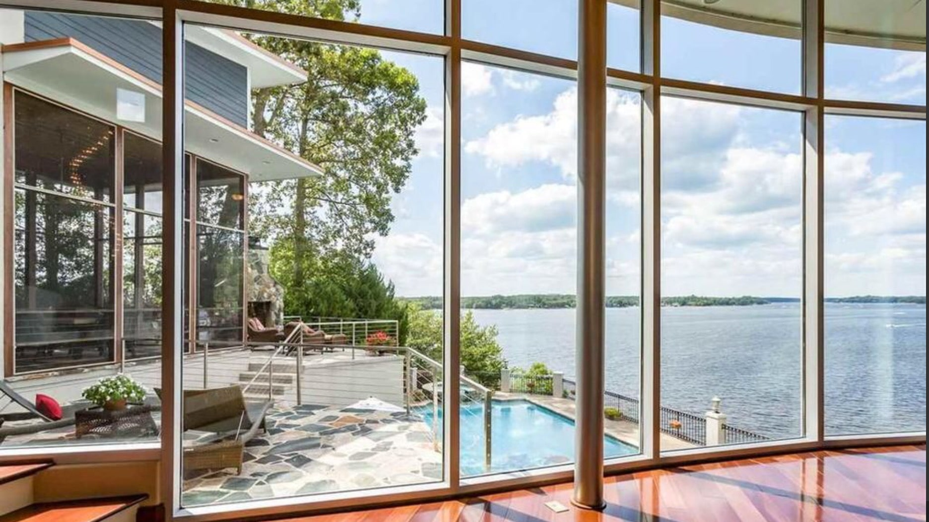 Curved floor-to-ceiling glass windows for expansive views of the lake.