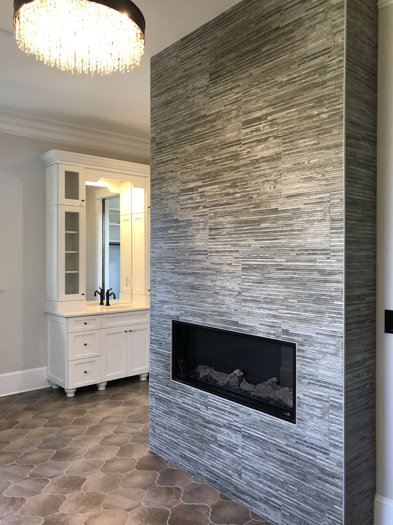 Master Bathroom - the amazing arabesque floor tile and gorgeous chandelier contrast perfectly with the old wood look of the tiled fireplace.