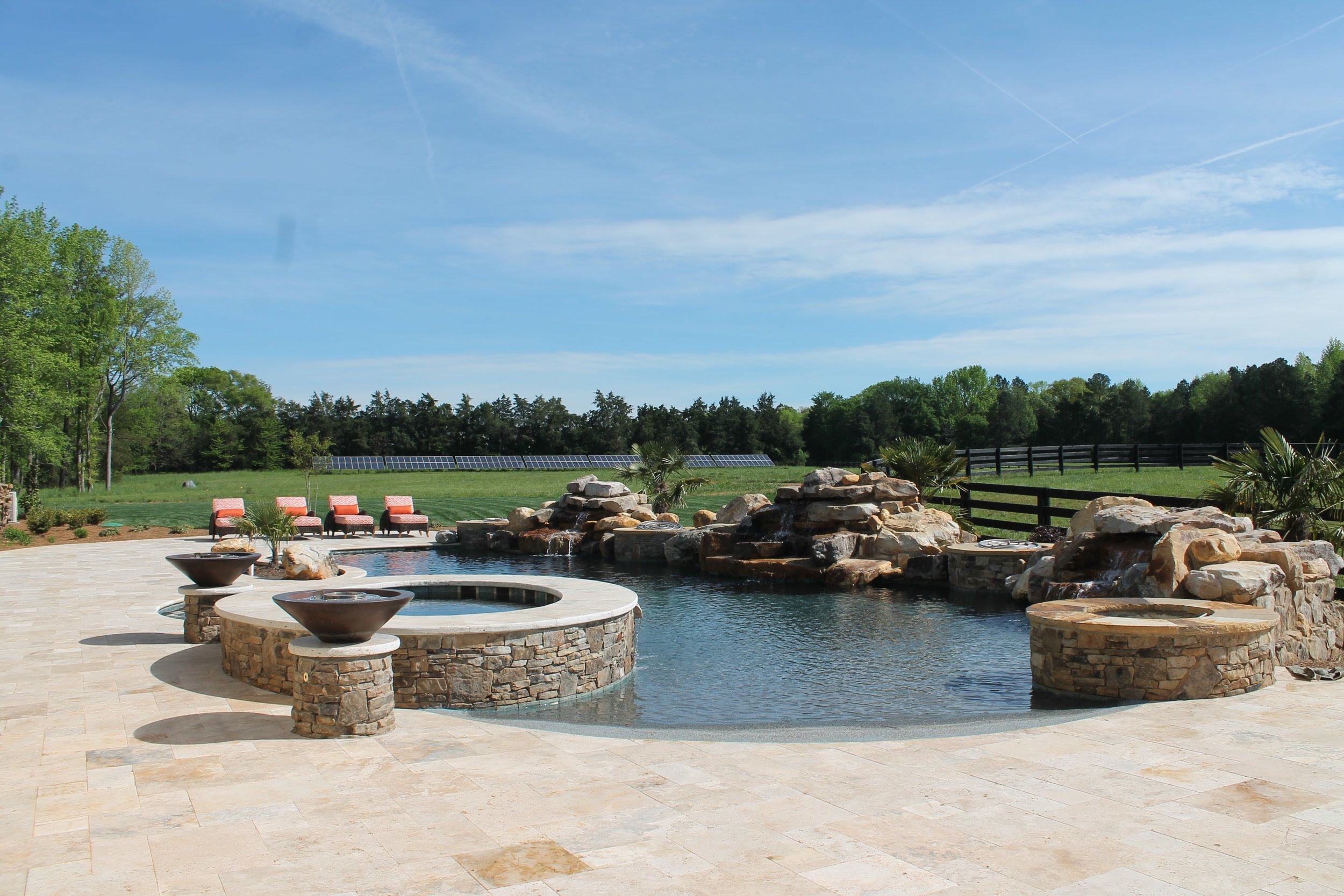 Custom salt water pool with waterfalls, large hot tub and fire bowls.