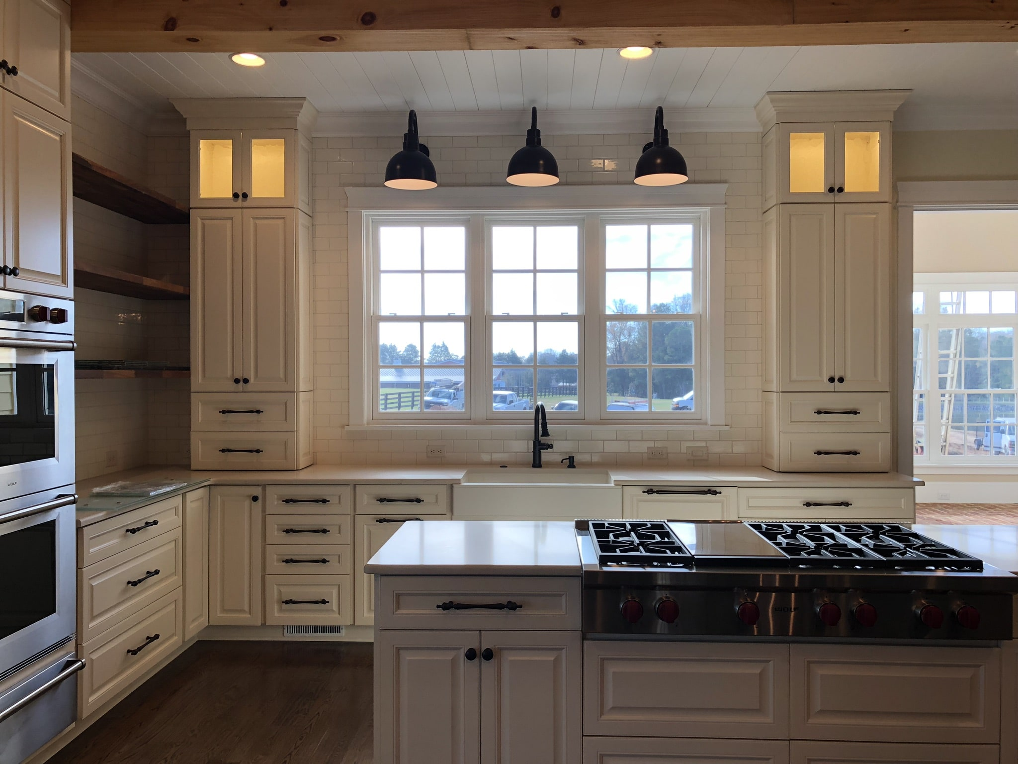 Custom kitchen with quartz counter tops, floating wood shelves and farm sink.
