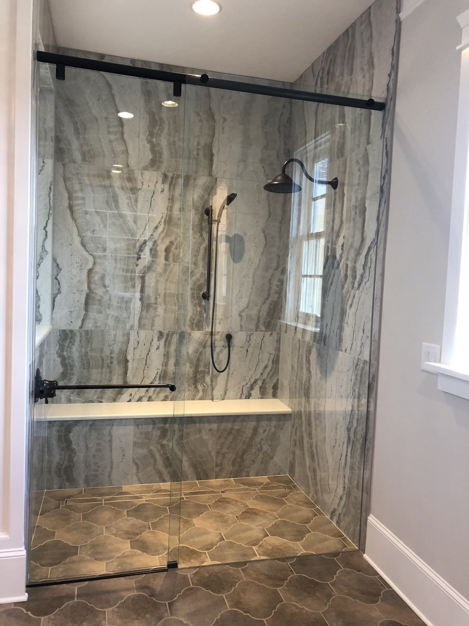 Zero entry shower in master bath with beautiful, large wall tile and sliding glass enclosure.  The custom linear drain was filled in with tile to provide a seamless look.