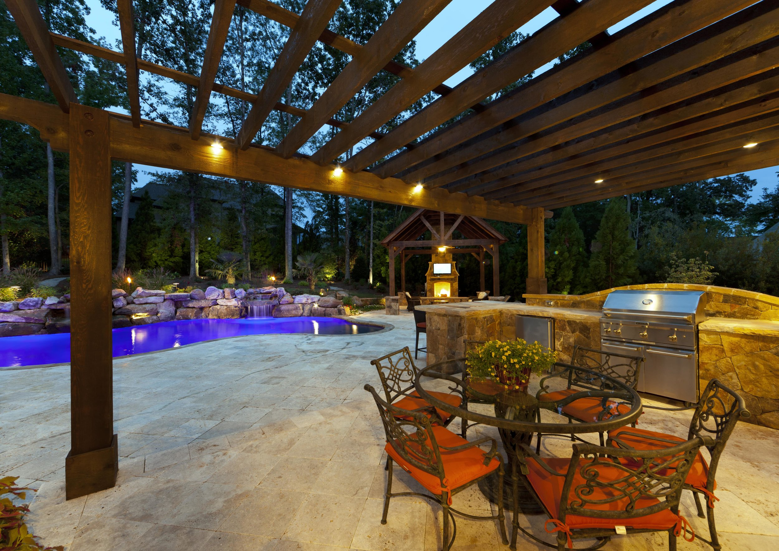 Such a great outdoor space was added for this family.  Pergola over the dining and grilling areas far enough away from the pool to keep the adults dry.  The cabana with TV, fireplace, and relaxing seating, provides yet another place for the adults to relax when not in the pool.  The travertine pool decking flows seamlessly into all areas.