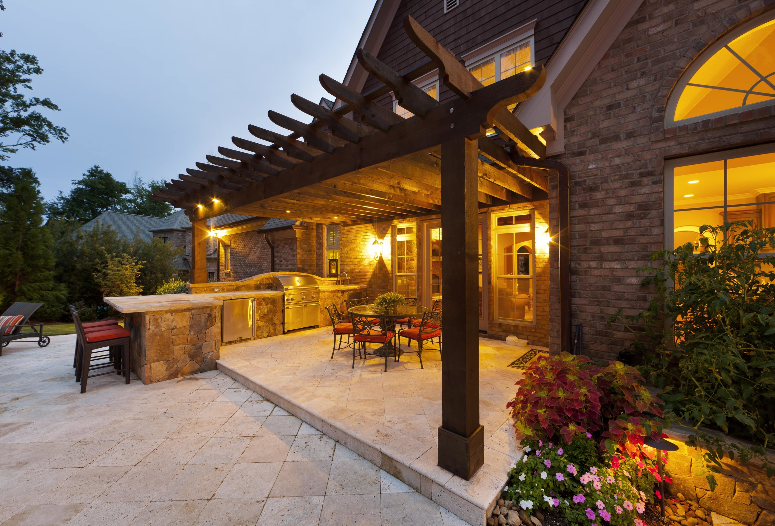 The travertine pool decking flows seamlessly up to the raised dining and grilling space. Plenty of space for a crowd to hang out and eat dinner.