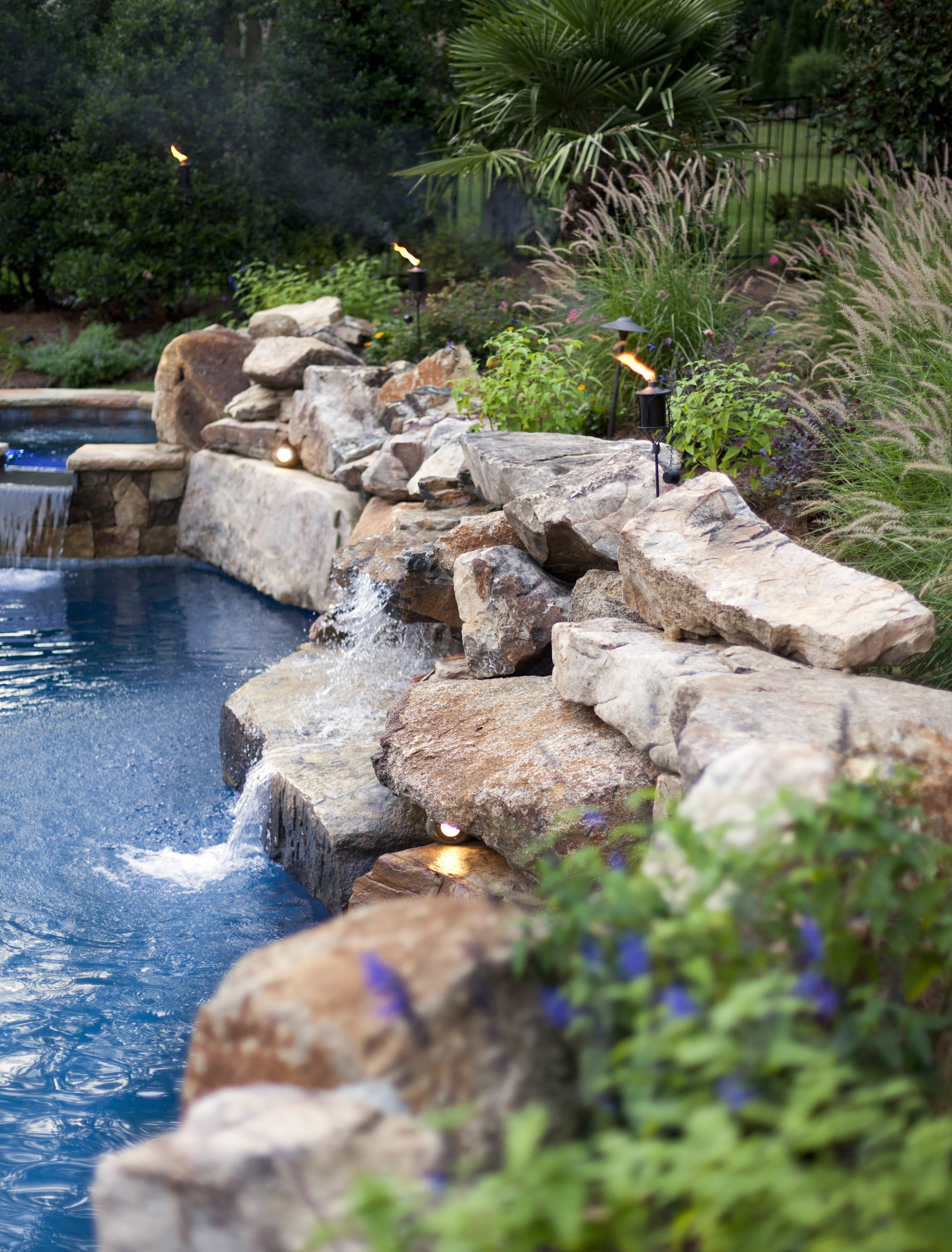 The natural boulders used in this pool, along with the waterfalls, provide a serene and relaxing atmosphere.