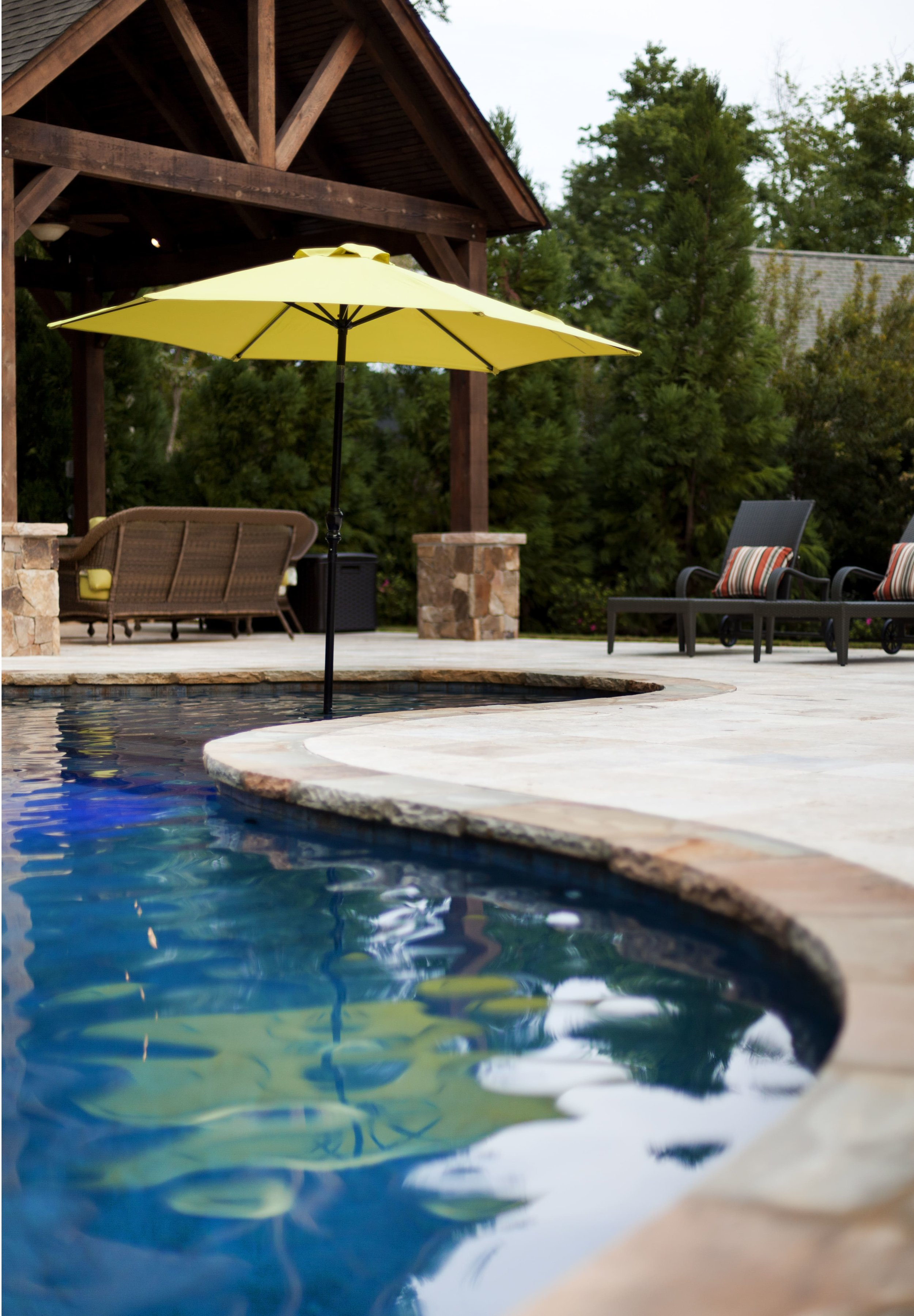 Chiseled edge on the stone coping ties in to the rustic feel of all the stained wood around. The umbrella that is in the pool provides shade for those who want it, while still allowing them to be in the pool.