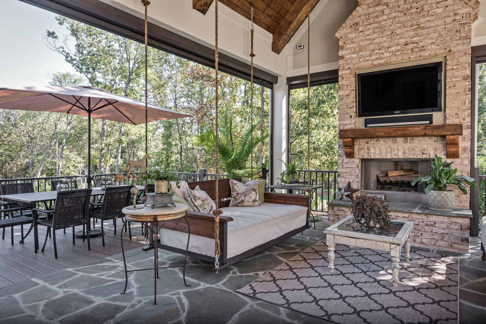 This screen porch is a thing of beauty.  The flagstone floor, brick fireplace, and rustic wood mantel give it a natural and relaxing feel.  The hanging beds provide a great place for a nap on a lazy day.