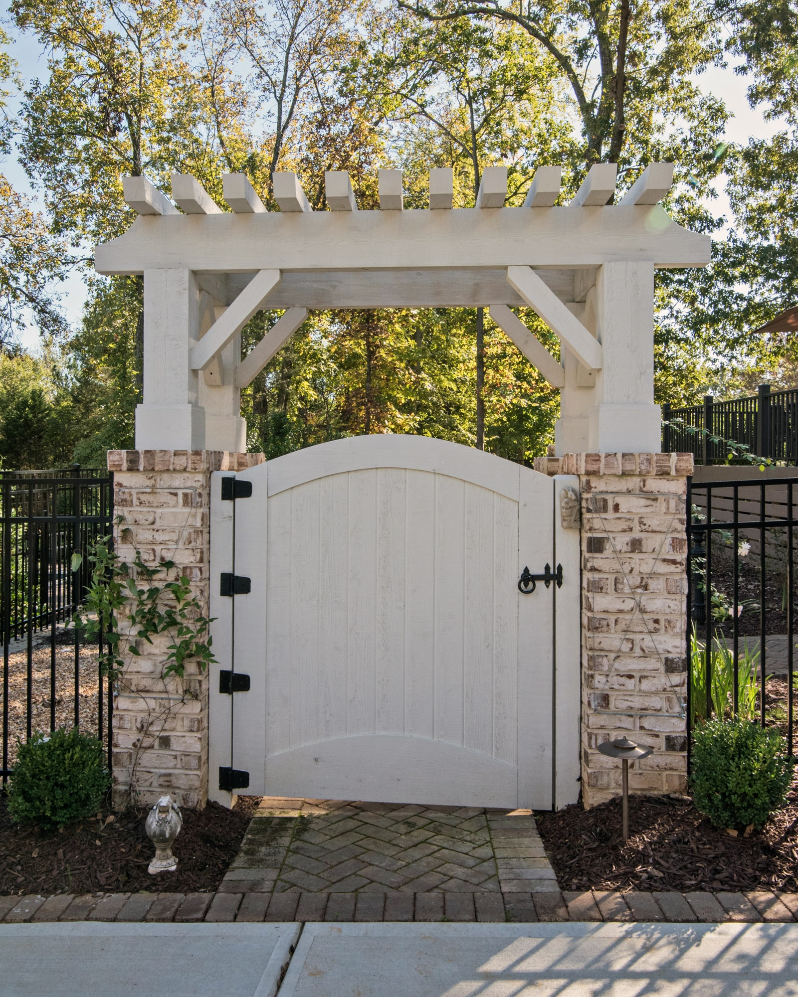 Beautiful pergola at the gate into the back hard ties in to the home and the landscaping perfectly.
