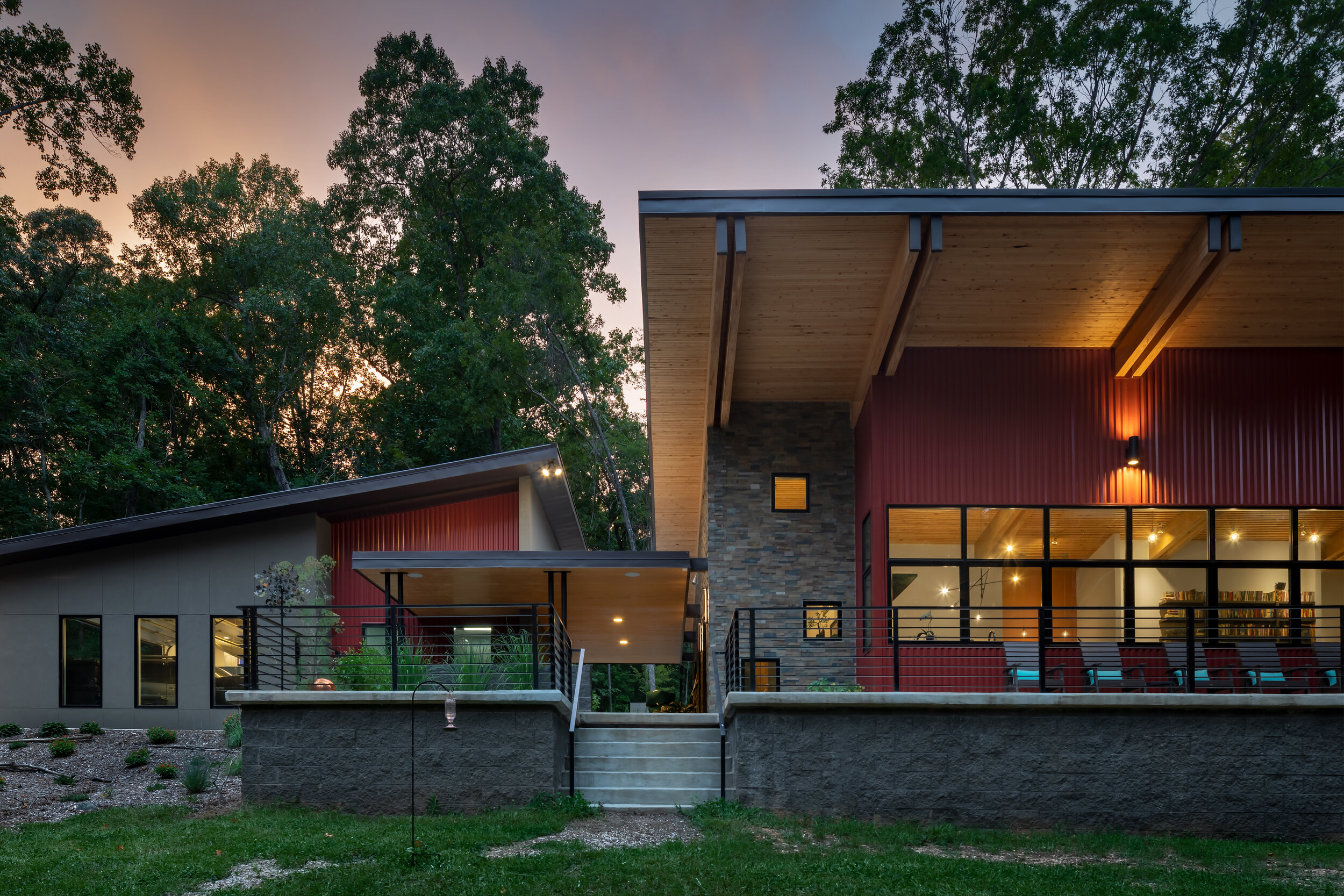 The exterior of this unique, contemporary home is highlighted by the red metal siding which pops against the more traditional stucco and stone.