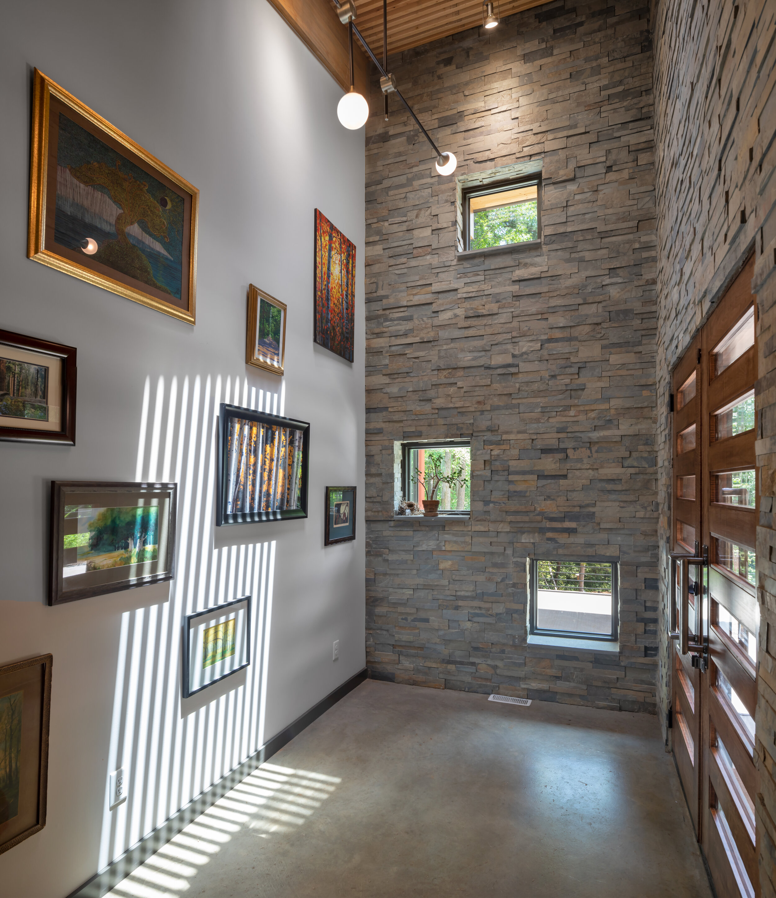 Foyer details - polished concrete floor, stone walls, skylight, art gallery wall and vaulted ceiling.