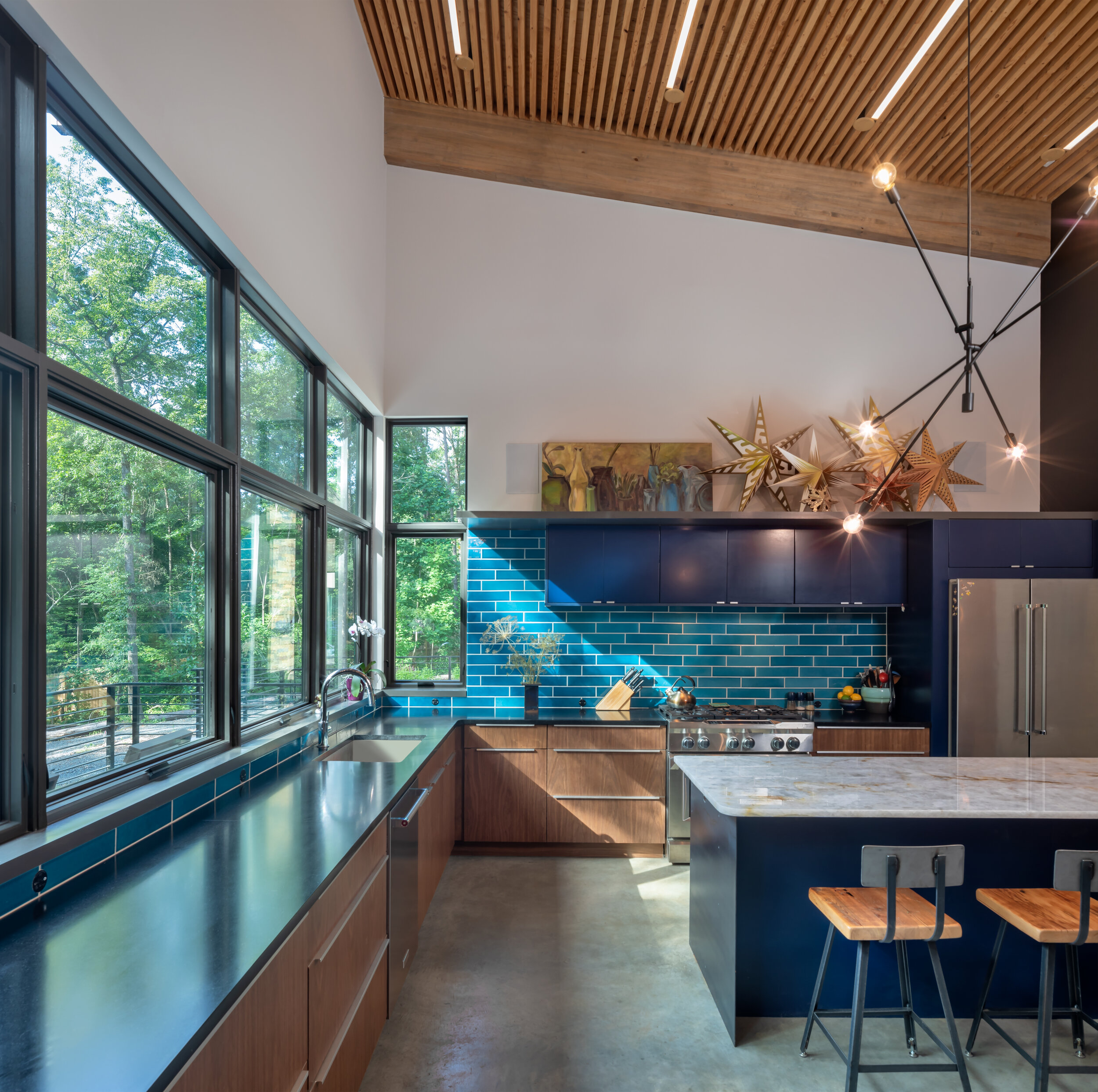 Kitchen details - expansive windows, custom blue cabinets, hand made subway tile, and slat wood ceiling with lights tucked between.