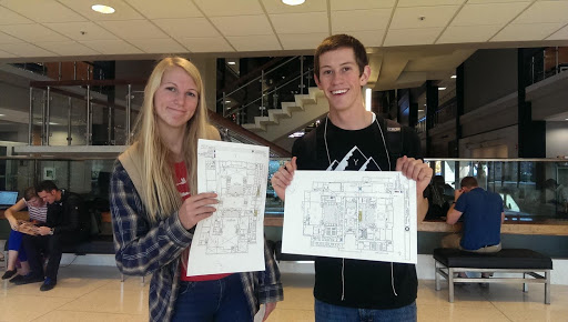 Male and female student, each holding up a map, in a building at BYU.
