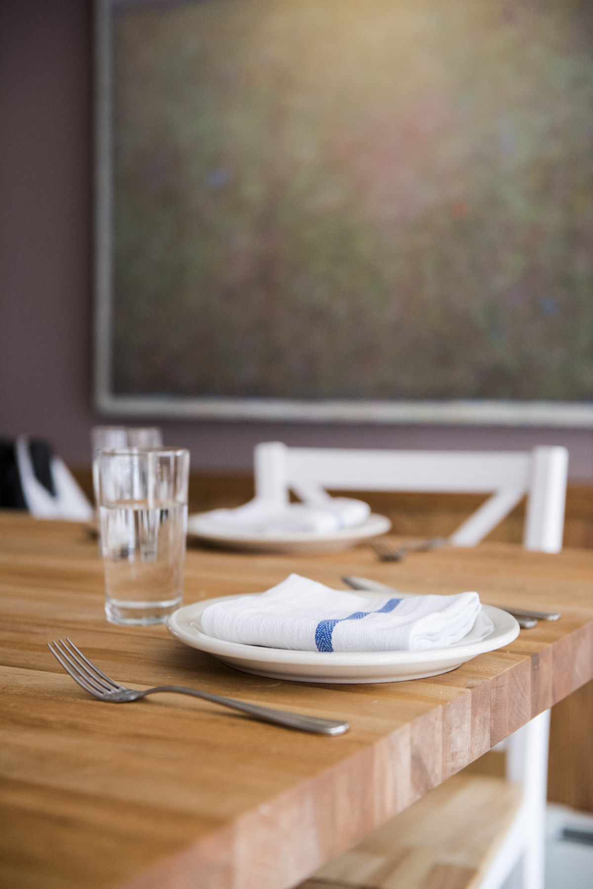 lightwoodendiningtable-with-silverware-table-settings-and-glass-cup.jpg