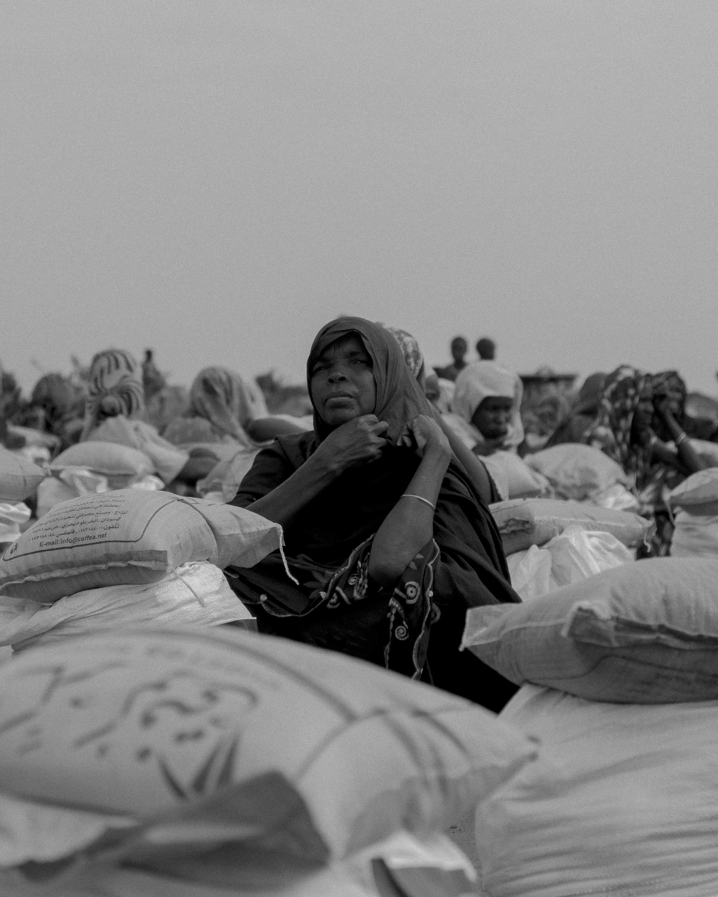 Women, displaced from war, wait to be able to leave with their food parcels in the El Serif refugee camps.