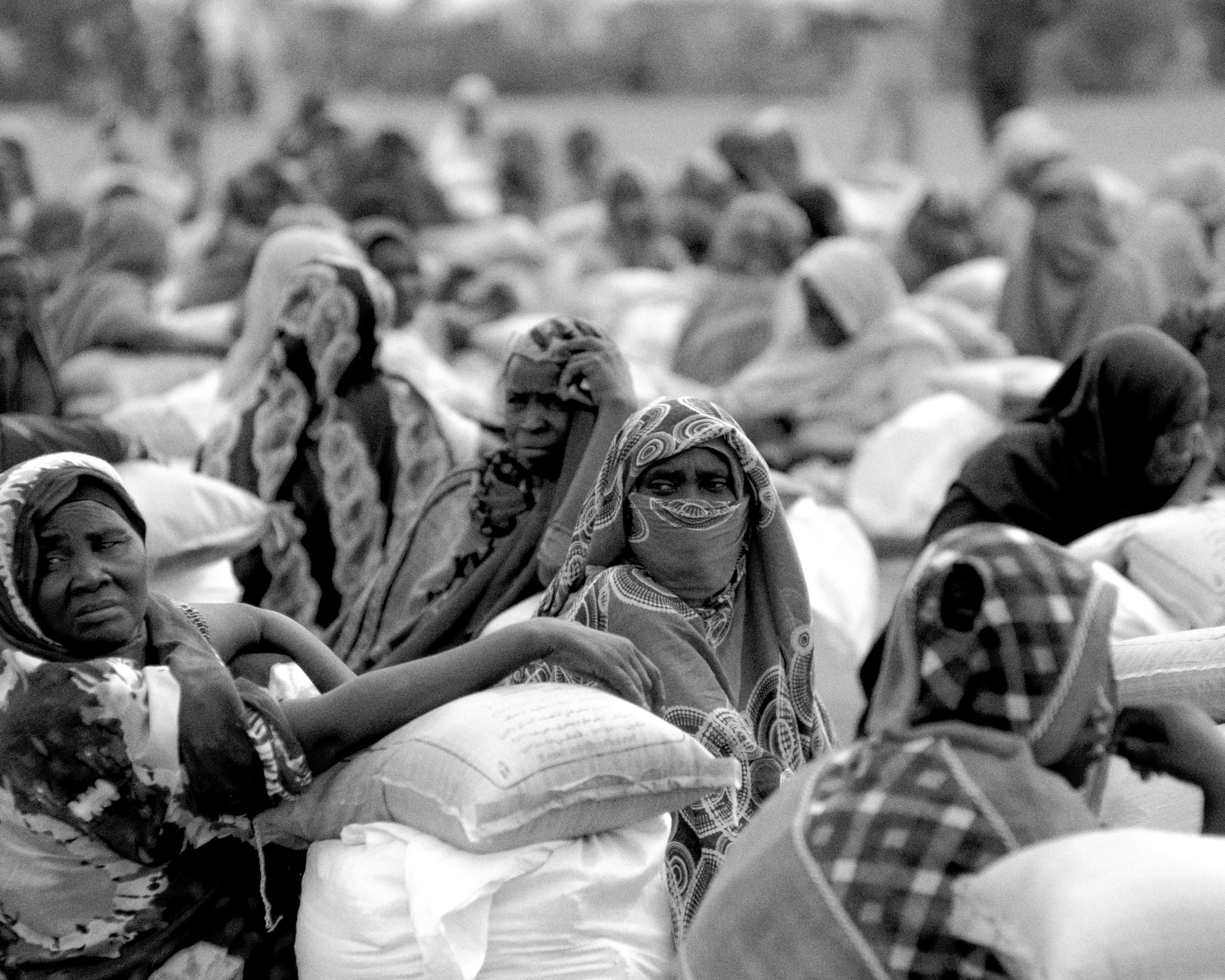 Women, displaced from war, wait to be able to leave with their food parcels in the Hotash refugee camps.
