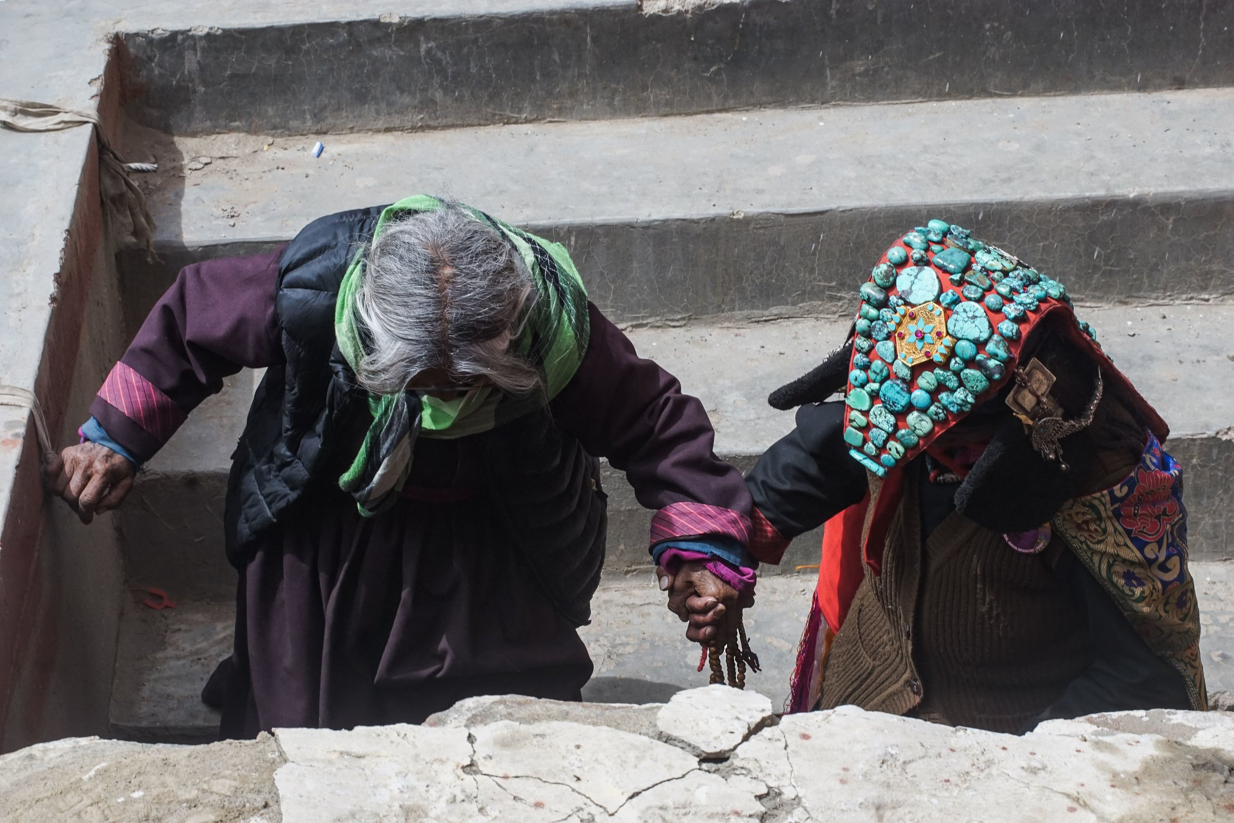 Changpa woman wearing traditional Ladakhi attire assists elder during local Buddhist festival.