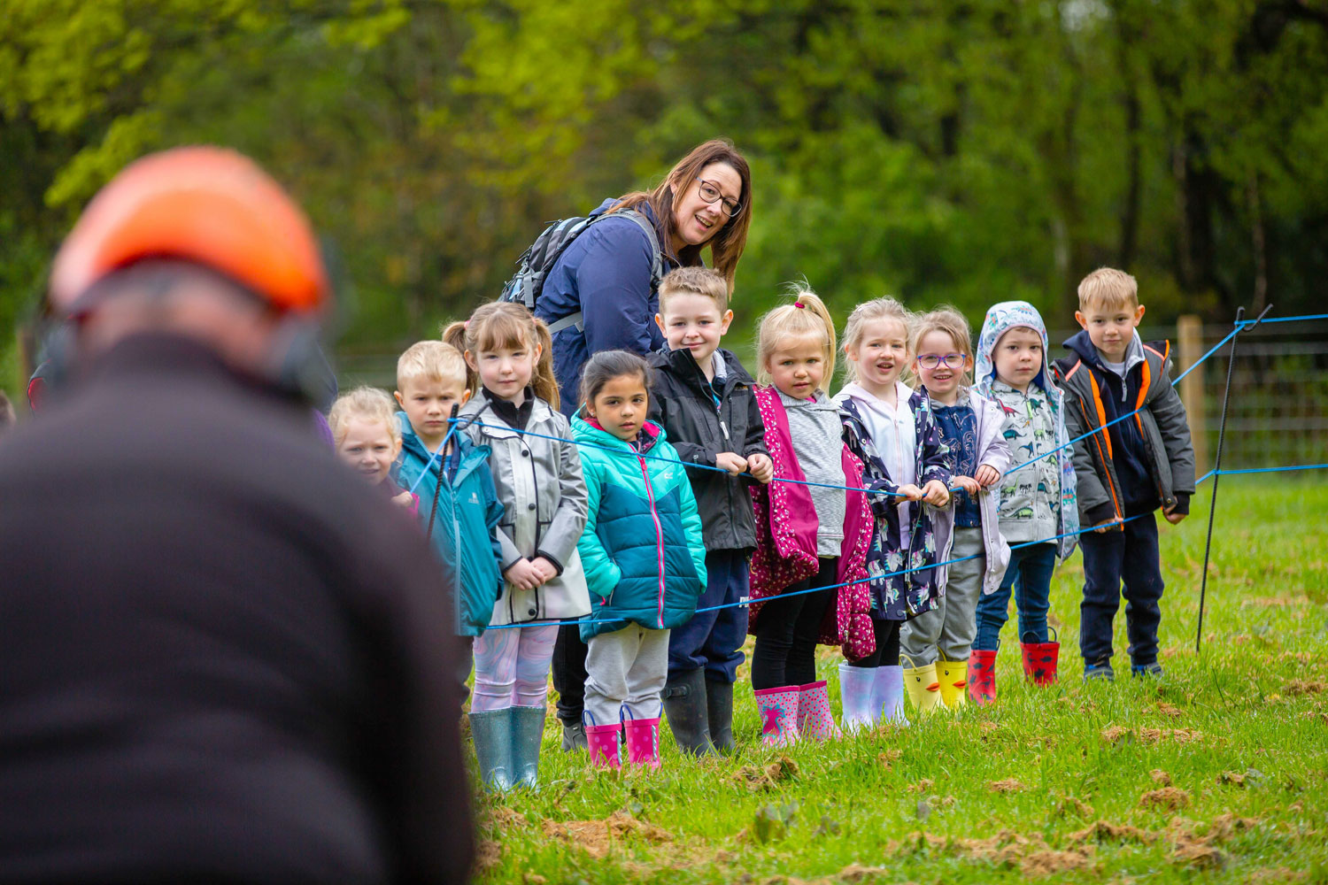 School children watch on during a chain saw demonstration at Great Grounds Education Centre.