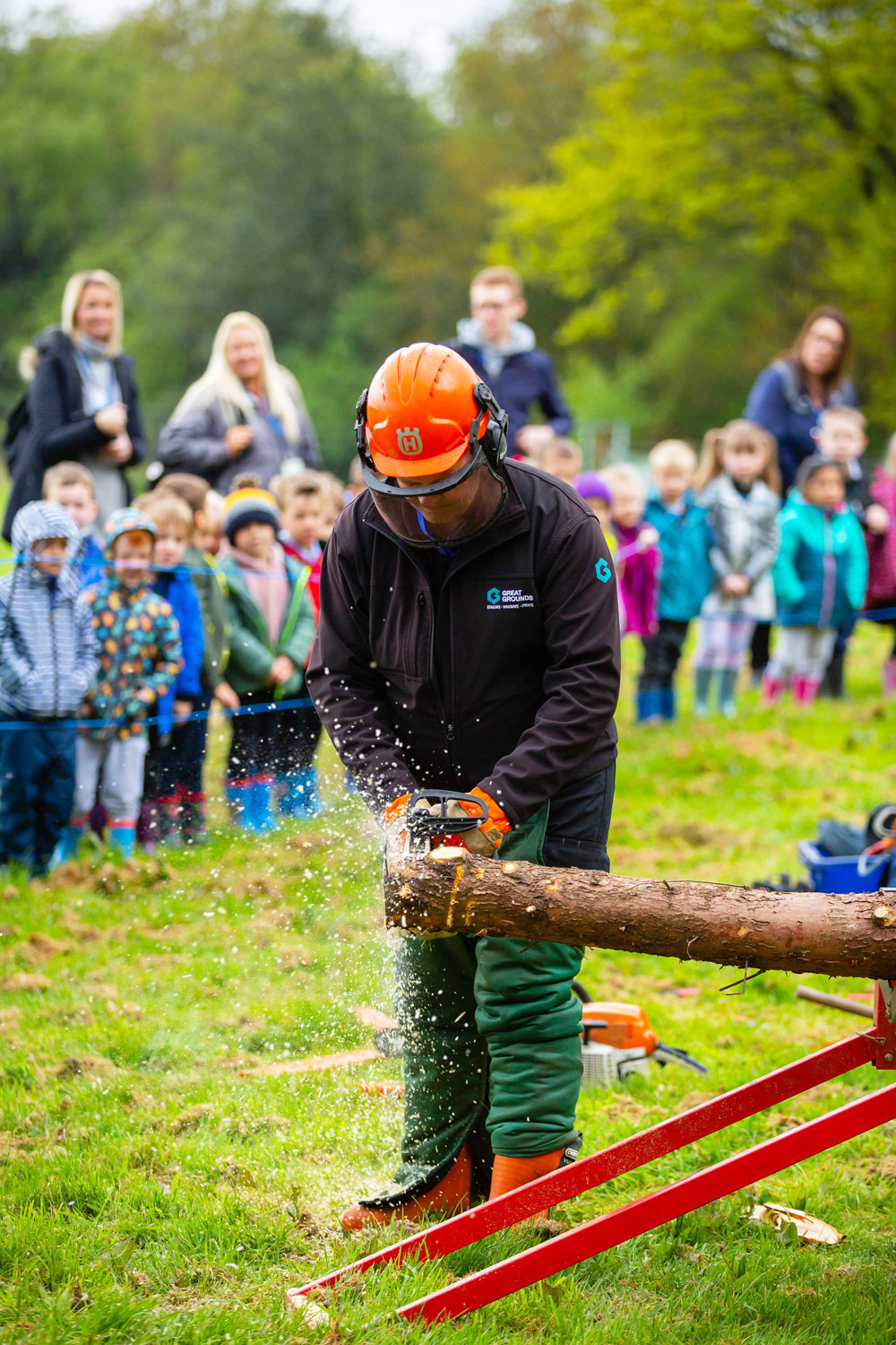 The children are given a chain-saw demonstration by one of the grounds maintenance team.