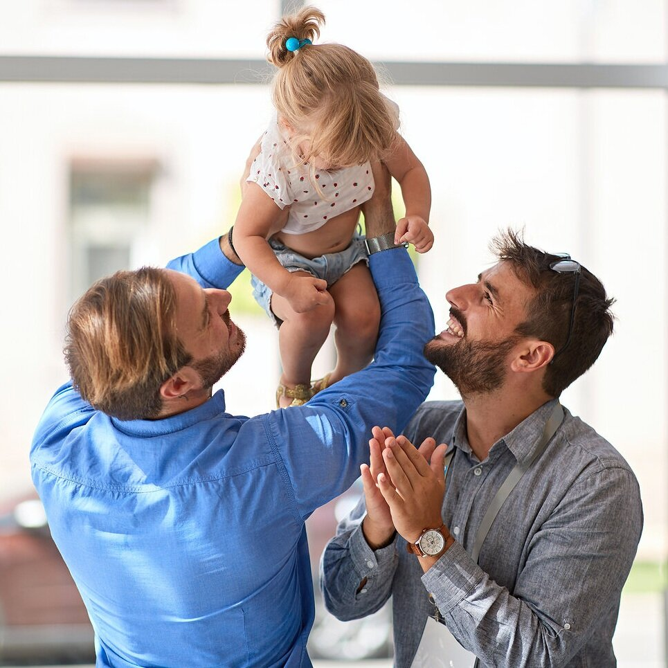 Photo with happy, smiling couple of two men with female child | LGBTQ couples counseling and parent coaching