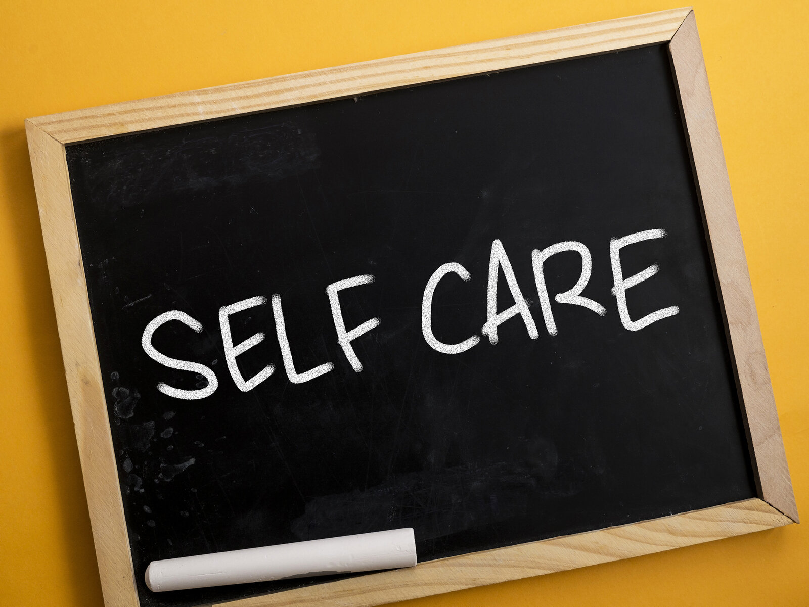 """Wooden framed chalkboard and chalk image with """"Self Care"""" written on the blackboard, for counseling and therapy"""