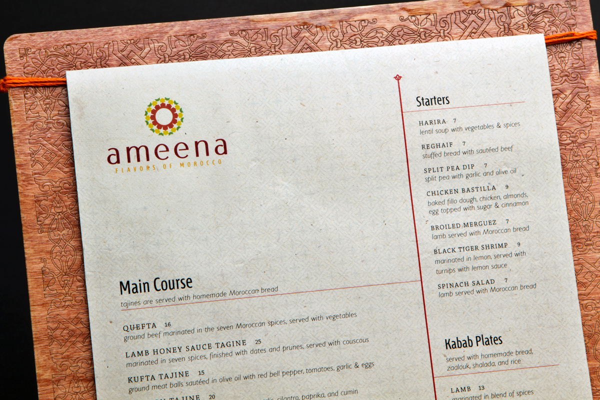Close-up of dinner menu. Details on paper and wood carving around the border can be seen.