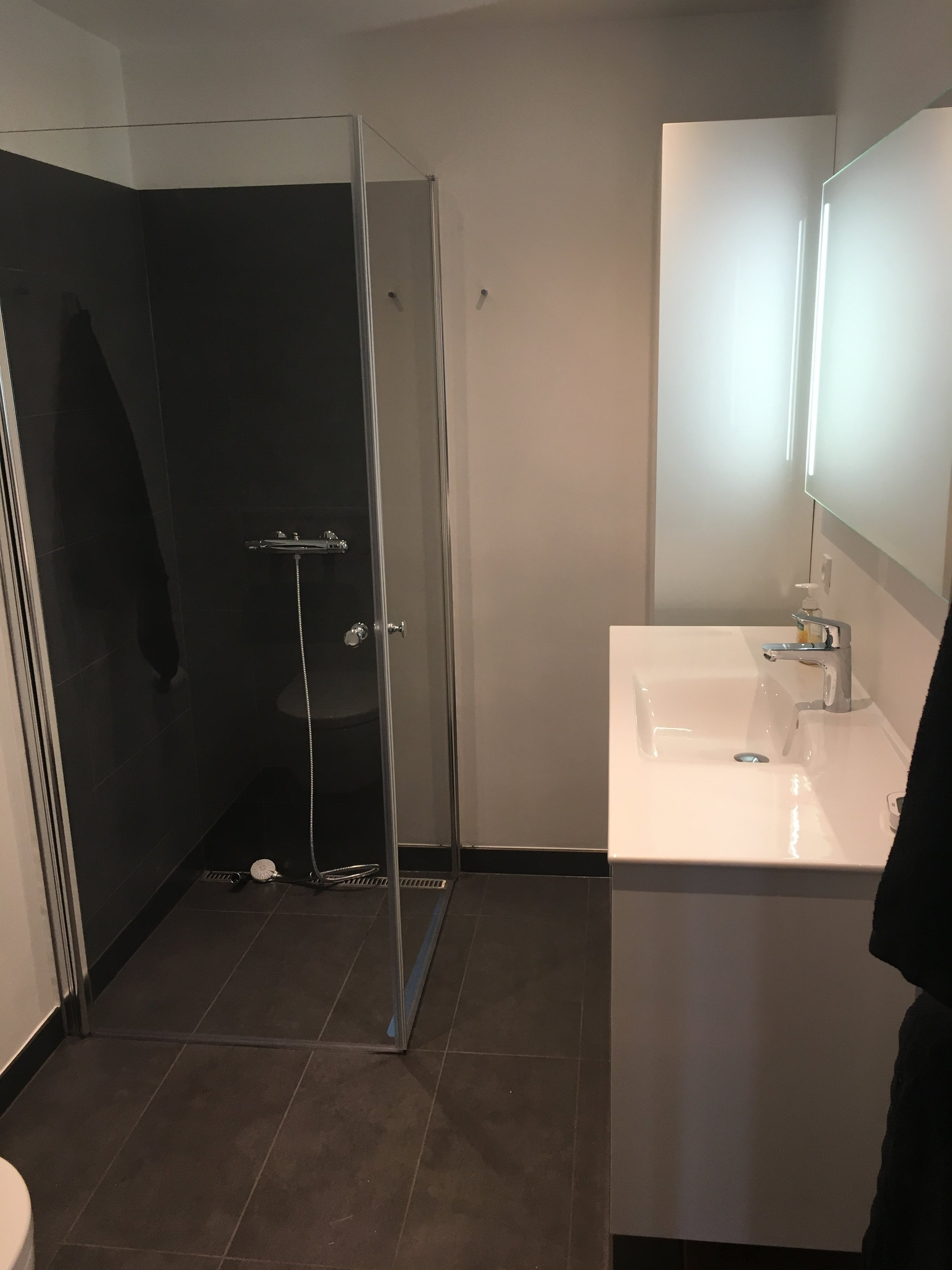 Totalenterprise - Badeværelse med nedsænket bruseniche med Unidrain og brusehjørne, Ifø Sense håndvaskemøbel.