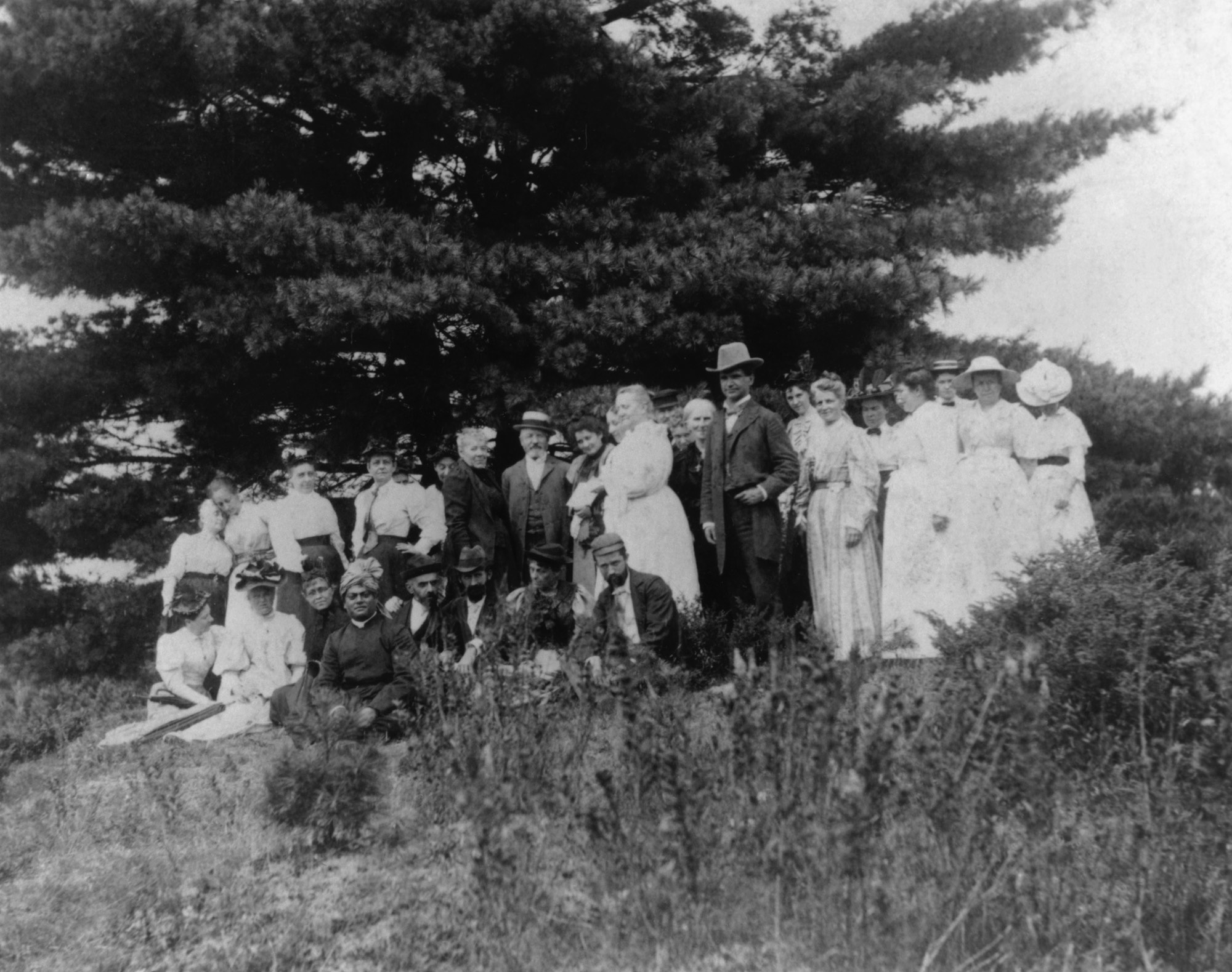 """(#30) Green Acre, August 1894. Swamiji is seated under the """"Swami's Pine"""" at Green Acre, Maine. This picture of the group under the tree was taken by Cora Stockham."""