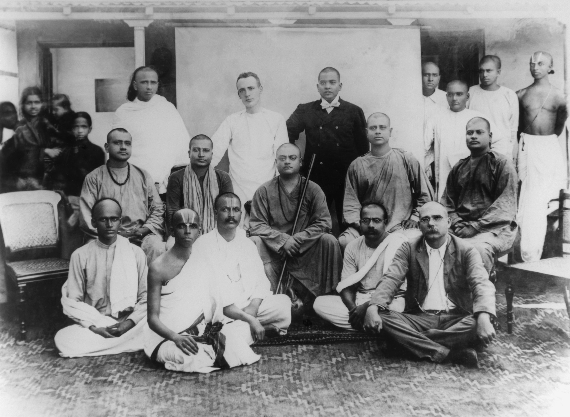 (#57) Chennai, February 1897.  Sitting on chair  ( from  L): Tarapada (a monk from another Order), Swami Shivananda, Swamiji, Swami Niranjanananda, Swami Sadananda.  Standing  ( from  L): Alasinga Perumal, J. J. Goodwin, M. N. Banerjee, and other devotees.  Sitting  ( from  L): (second) Biligiri Iyengar, (fourth) M. C. Nanjunda Rao.