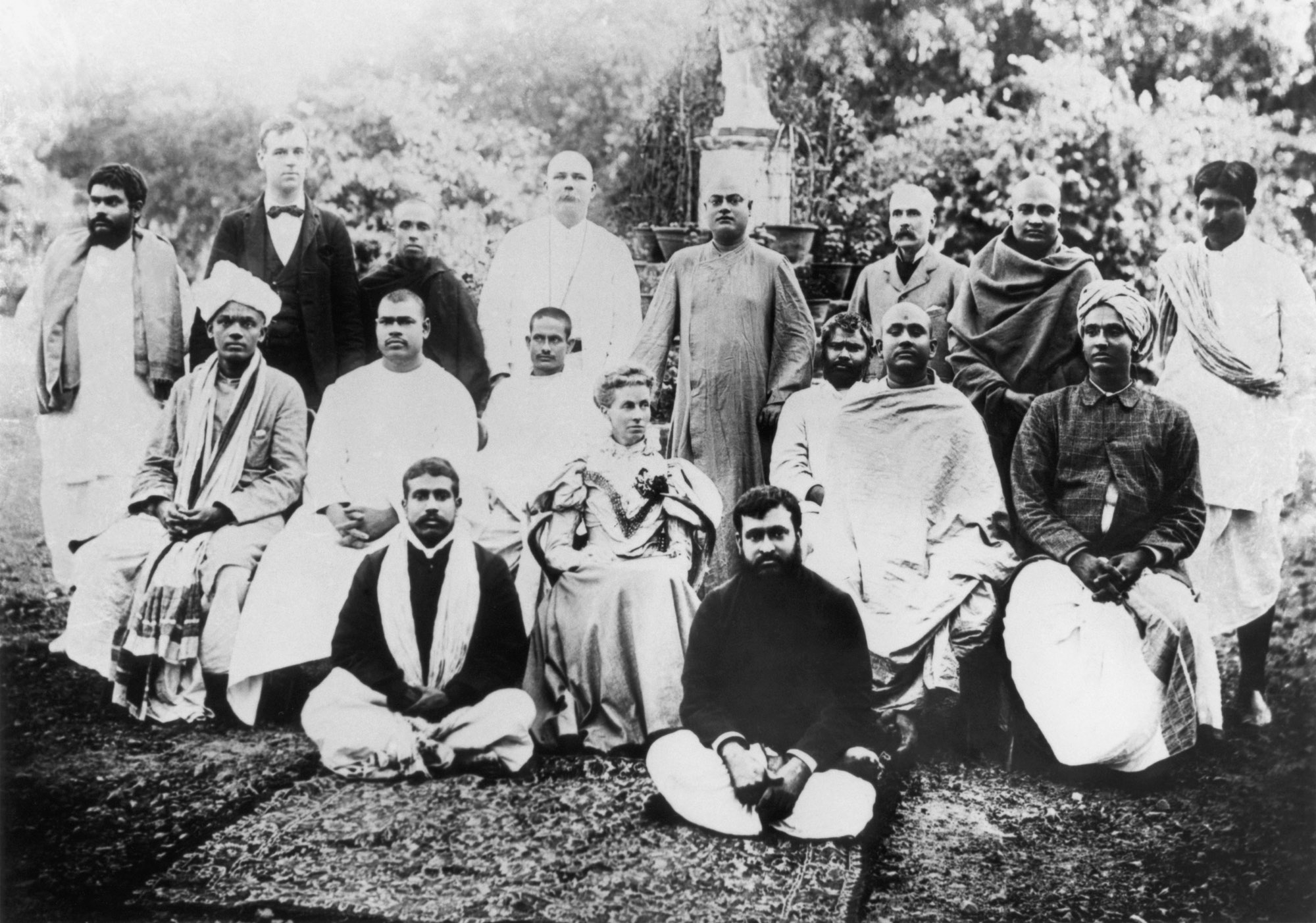 (#65) Kolkata, February 1897.  Standing  ( from  L): Shantiram Babu, Mr. Turnbull, Swami Prakashananda, [unidentified], Swamiji, Capt. Sevier, Swami Shivananda, [unidenfitied].  Sitting  ( from  L): Alasinga Perumal, Swami Ramakrishnananda, Swami Premananda, Mrs. Sevier, Swami Adbhutananda, Swami Turiyananda, G. G. Narasimhachariar.  Floor  ( from  L): [unidentified], Mr. Harrison from Colombo.