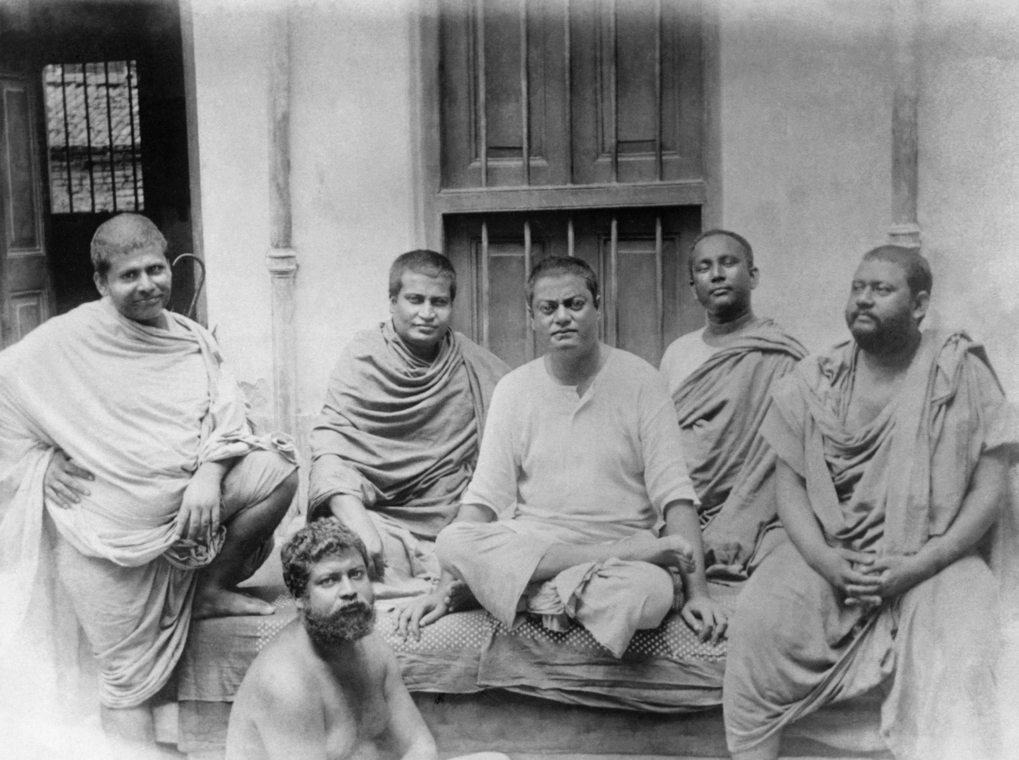 (#75) Kolkata, (June 20?), 1899. This picture was taken at a rented house (8 Bosepara Lane, where Holy Mother was staying at the time.  ( From  L): Swami Trigunatita, Swami Shivananda, Swamiji, Swami Turiyananda, Swami Brahmananda, and ( seated below ) Swami Sadananda.