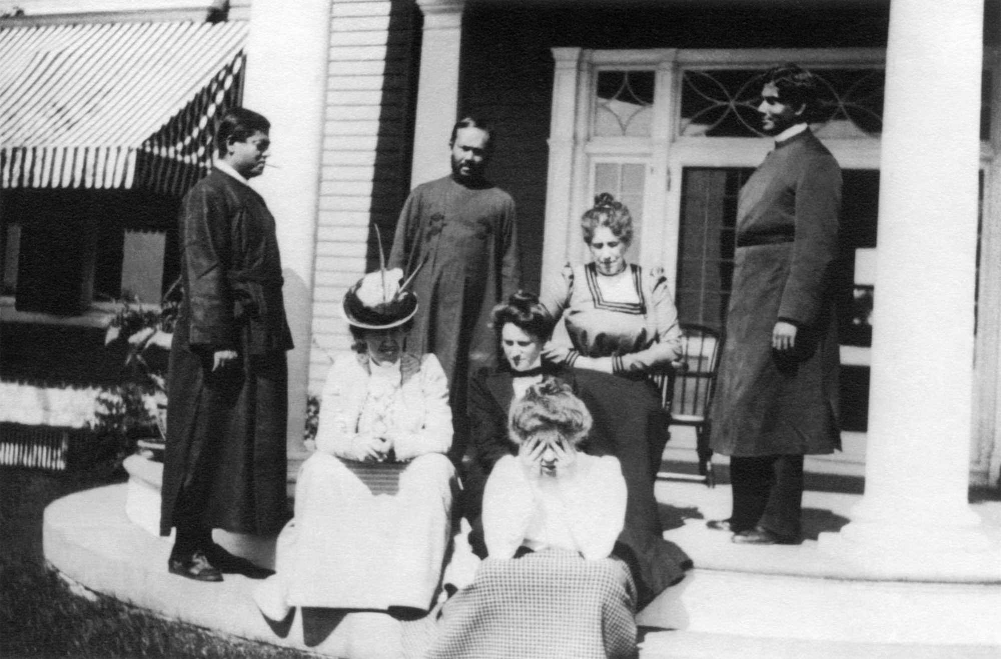 (#78) Ridgely Manor, New York, September 1899. Same group, same day as #77. We see Swamiji standing and looking unwell, and Alberta with her face in her hands, shielding her eyes from the afternoon sun.