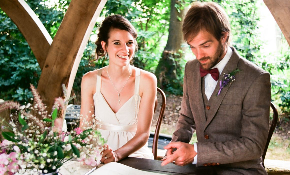 A groom looks at a reception book whilst the bride smiles.