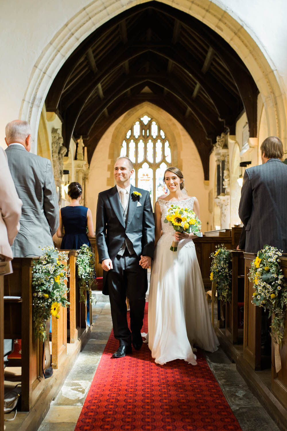 A-bride-and-groom-walk-down-the-aisle-at-a-wedding-in-Dumbleton.jpg