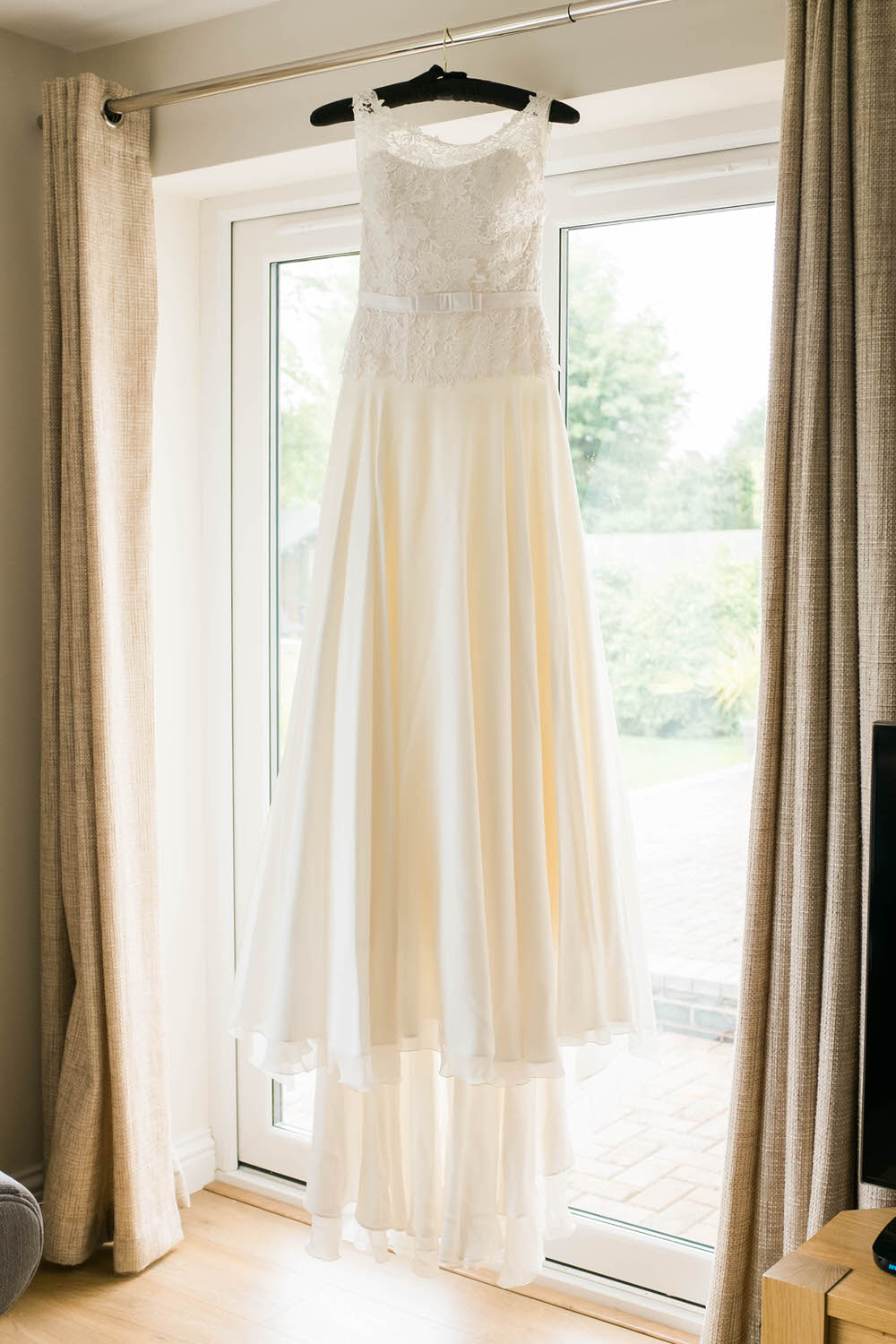 A-brides-wedding-dress-hung-in-a-window-in-Cheltenham.jpg
