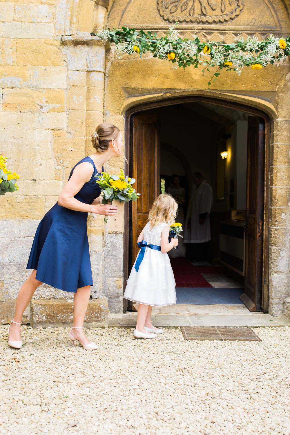 A-flower-girl-waits-for-the-bride-and-groom-in-Dumbleton.jpg