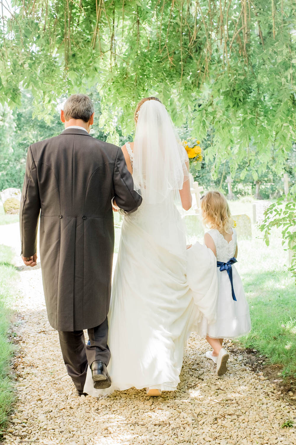 The-bride-and-father-walk-to-a-church-in-Dumbleton.jpg