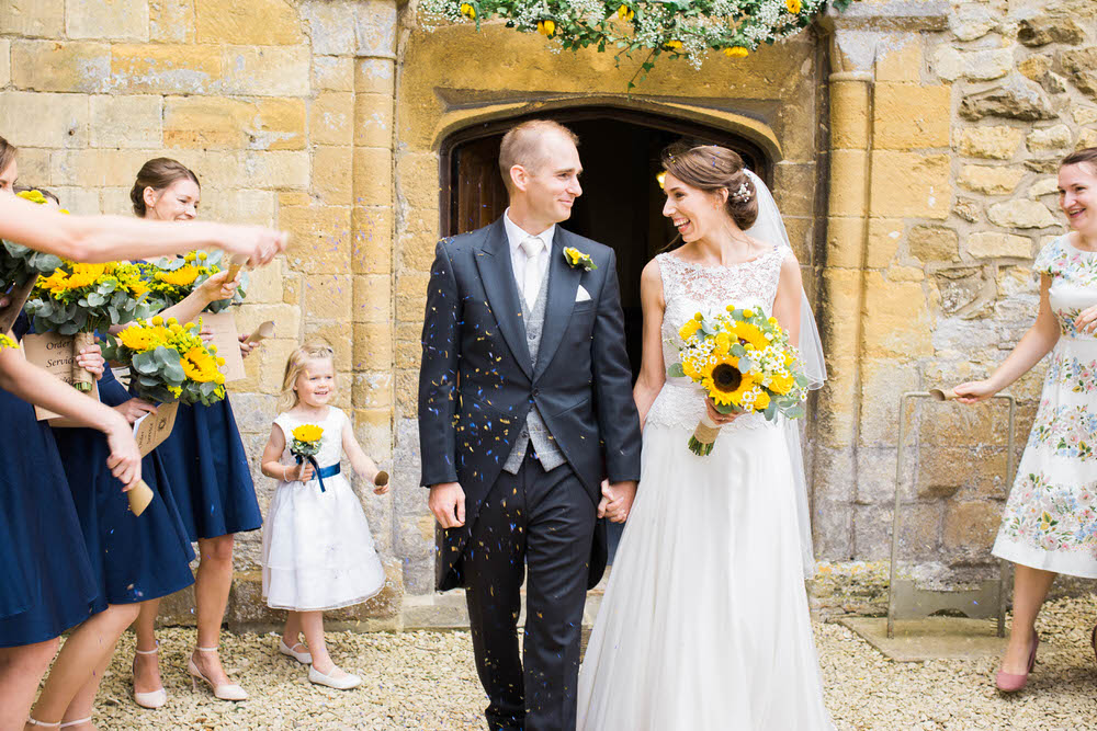 The-bride-and-groom-leave-a-church-to-confetti-in-Dumbleton-England.jpg