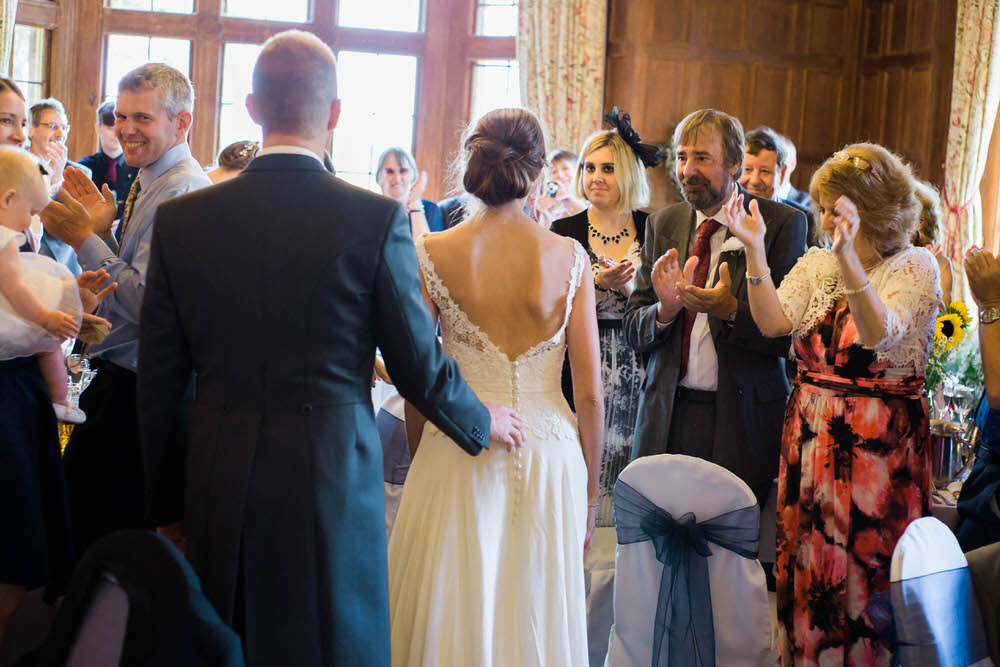 The-bride-and-groom-walk-to-their-seats-at-a-wedding-in-Cheltenham.jpg