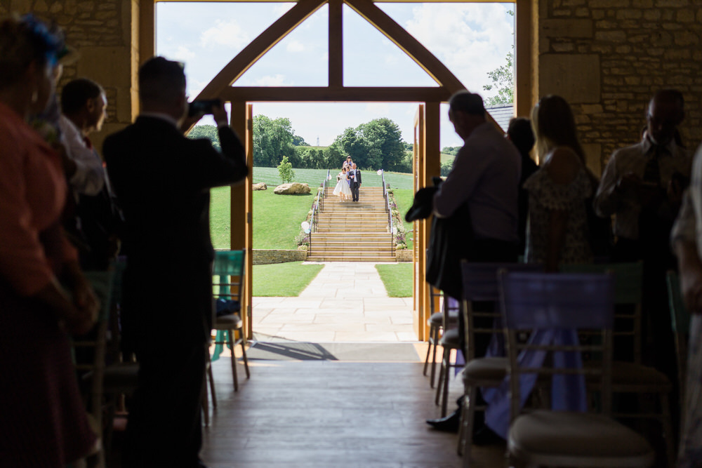 Special-Day-Photography-The-Barn-At-Upcote-Cheltenham-The-bride-walking-down-the-aisle-at-The-Barn-At-Upcote.jpg